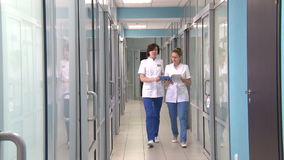 Two doctors walking down the hallway at the clinic. 20.08.2015.Russia,two doctors walk along the corridor in the hospital,medicine.laser therapy stock footage