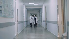 Two doctors walking on hospital`s corridor and advising. 4K