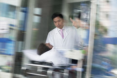 Two doctors wheeling in a patient on a stretcher through the doors of the hospital Stock Images