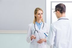Two doctors in white coats discussing diagnosis. In clinic royalty free stock images