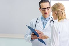 Two doctors in white coats discussing diagnosis. In hospital royalty free stock photography