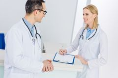 Two doctors in white coats discussing diagnosis. In hospital stock images