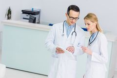 Two doctors in white coats with tablet discussing diagnosis. In clinic royalty free stock images