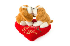 Two dogs kissing - toys with valentine's heart. Two toy dogs kissing sitting on a pillow in form of valentine's heart Royalty Free Stock Photo
