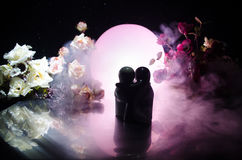 Two doll hugging on table with flowers and moon decoration Lighted background with smoke.Love concept. Greeting or gift card desig. N idea. Silhouette of hugging Stock Photos
