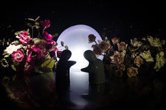 Two doll hugging on table with flowers and moon decoration Lighted background with smoke.Love concept. Greeting or gift card desig Stock Image