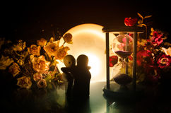 Two doll hugging on table with flowers and moon decoration Lighted background with smoke.Love concept. Greeting or gift card desig Stock Photography
