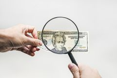 Two dollar bill and magnifying glass on white. Men`s hands hold 20 dollars and a magnifying glass. verification of the authenticity of the American banknote royalty free stock photo