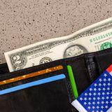 A two dollar bill reach out out of a black old purse. And also p. Art of the American flag. Square. Close-up stock photo