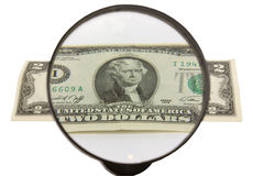 Two dollars and magnifying glass Stock Photography