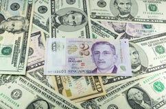 Two dollars singapore on many dollars background Stock Photography