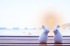 Two dolls sitting on wooden table at beach lounge Stock Images