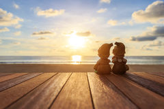 Two dolls sitting on wooden table at sunset beach Royalty Free Stock Image