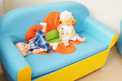 Two dolls on a small sofa Stock Image