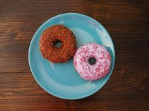 Two donuts on the blue plate stock images