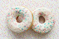 Two donuts with colorful sprinkles and glazes surface over colorful background. Like sweet dessert food background - close up of home made sweet stock photo