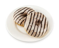 Two donuts with icing on a white plate Stock Image