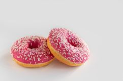 Two donuts with pink icing on a white background stock photo