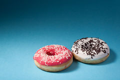Two donuts with red and white icing  on blue background Royalty Free Stock Photos