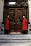 Two doormen outside a hotel`s entrance. Doormen smiling at each others in full uniform outside a hotel Royalty Free Stock Photo