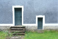 Two doors in blue. Two doors - big and small - in the blue wall royalty free stock photography