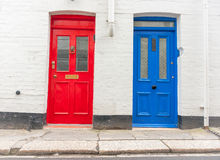 Two doors similar but not the identical. Two traditional style doors together different colors facing the street Royalty Free Stock Image