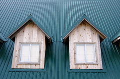 Two dormer with windows on the green roof Stock Images