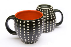 Two dotted coffee mugs. Two coffee mugs which are dotted on the outside and red on the inside Stock Images