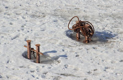 Two double bitt bollards with chain and metal rope in frozen river Royalty Free Stock Images