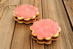 Two double round sand cakes decorated with pink icing and jam on Royalty Free Stock Photo