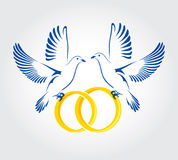 Two Doves flying with wedding rings Royalty Free Stock Photography