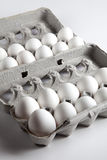 Two Dozen White Eggs Inside Egg Cartons. Photographs of two dozen eggs inside an egg carton on a white background stock photo