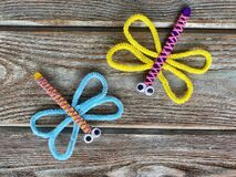 Two dragonflies, children`s crafts from pipe cleaners and wooden sticks with yarn