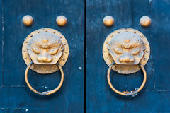 Two dragons chinese golden colored door knockers on a blue crack. Ed paint gate, Chengdu, Sichuan Province, China Stock Image