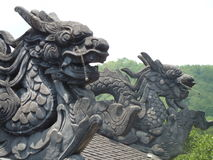 Two Dragons. Two grey stone dragons on a rooftop in Vietnam Stock Images