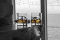 Two drams of whiskey on the rocks on fireplace mantel Stock Photo