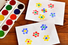 Two drawings with flowers, finger painting, children game. Colorful paint. Brown wooden background Stock Photography