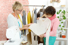 Two dressmaker looks at a nice sweater Royalty Free Stock Photos
