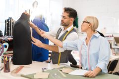 Two Dressmakers in Atelier. Side view portrait of two tailors measuring mannequin while making clothes in traditional atelier workshop, copy space stock images