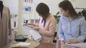 Two dressmakers are looking at clothes, standing in sewing studio, young women work together at table, in bright room. There is mannequin in dress, clothing stock video