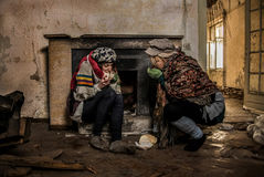 Two drifters eating bread at abandoned house royalty free stock photography