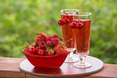 Two drinks, red drink, cherry, strawberry, raspberry. Ripe strawberry, cherry, raspberry in the red bowl, two glasses of soda on a green blurred background Stock Photography
