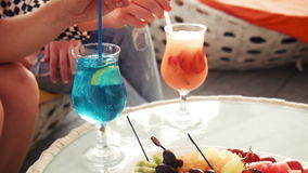 Two drinks on table near legs with copy space. Two icy fruit colored drinks on table with fruit appetizers near legs with copy space stock video footage
