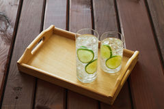 Two drinks on wooden tray with ice and condensation on glass Royalty Free Stock Image