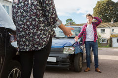 Two Drivers Arguing Over Damage To Cars After Accident. Two Drivers Argue Over Damage To Cars After Accident stock photo