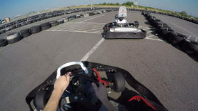 Two drivers drive go kart and overtaking on outdoor track, camera is attached to the helmet,. Man drives go kart on track, Karting filmed from the driver's view stock video footage