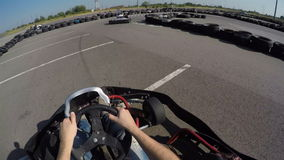 Two drivers drive go kart and overtaking on outdoor track, camera is attached to the helmet,. Man drives go kart on track, Karting filmed from the driver's view stock video