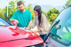 Woman and man friendly reporting the damage of the car after accident. Two drivers filling the accident report document after car crash stock photos