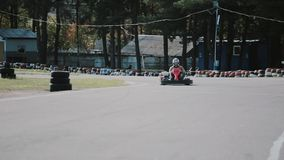 Two drivers on a go-kart track move into the camera and pass it by. Go-kart race. Go-kart race. Two drivers on a go-kart track move into the camera and pass it stock video footage