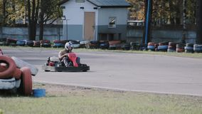 Two drivers on a go-kart track move passing by a long row of coloured tires. Go-kart race. stock video footage